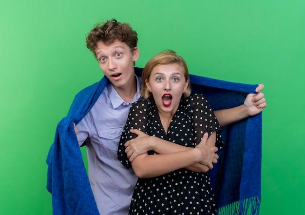젊은 아름 다운 부부는 녹색 벽 위에 격자 무늬 서에서 그의 냉동 여자 친구를 덮으려고 남자를 놀라게