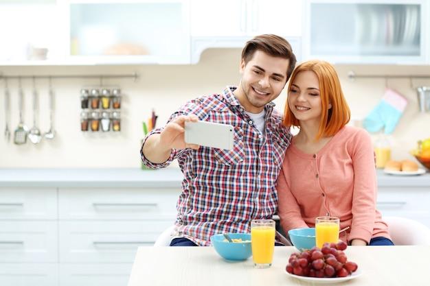 Молодая красивая пара делает селфи на кухне