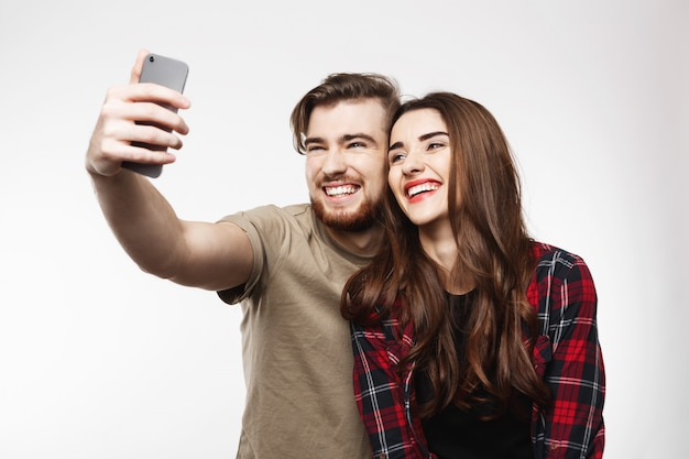 Giovani belle coppie che si fotografano, ridendo allegramente.