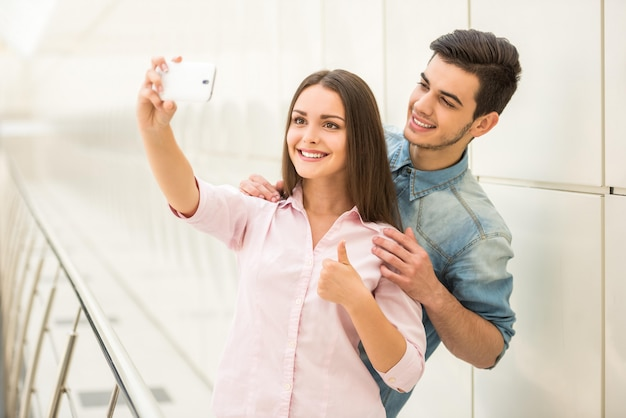Young beautiful couple taking selfie with smartphone.