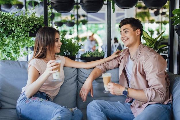 カフェの夏のテラスでコーヒーを飲みながら話している若い美しいカップル