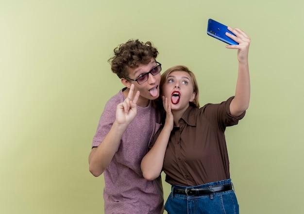 一緒に携帯電話を使用して若い美しいカップルは、舌を突き出して、光の上にvサインを見せて自分撮り笑顔を取ります