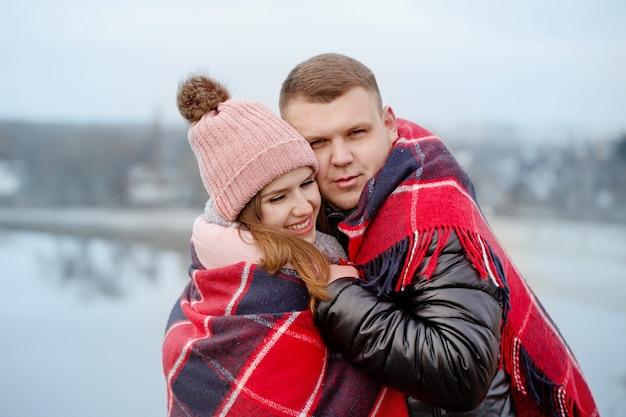 젊은 아름 다운 부부는 거리에서 따뜻한 담요에 피난했다