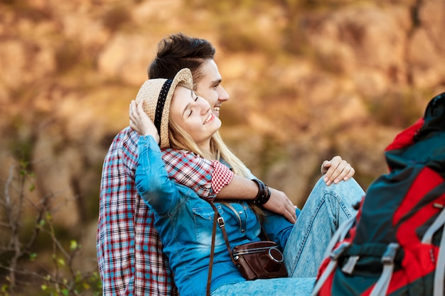 Young beautiful couple of travelers enjoying view of canyon, smiling