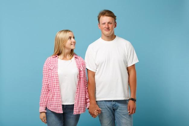 白いピンクの空の空白のtシャツのポーズで若い美しいカップル2人の友人の男と女