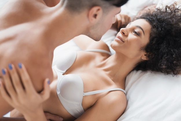 Young beautiful couple in underwear lying on bed