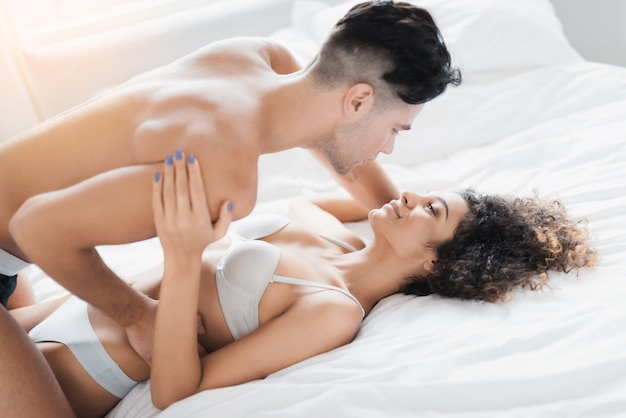 Young beautiful couple in underwear lying on bed.