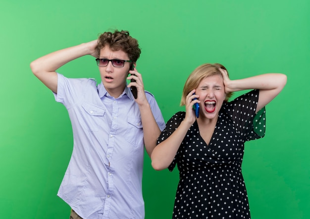 Young beautiful couple upset man and angry woman talking on mobile phones standing over green wall