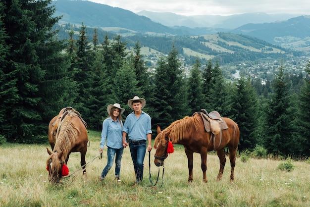 Молодая красивая пара гуляет с лошадьми в горах