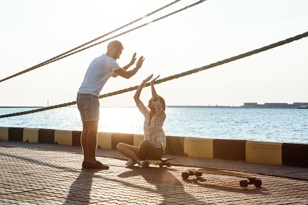 海辺を歩いて、ハイタッチ、スケートボードを与える若い美しいカップル。