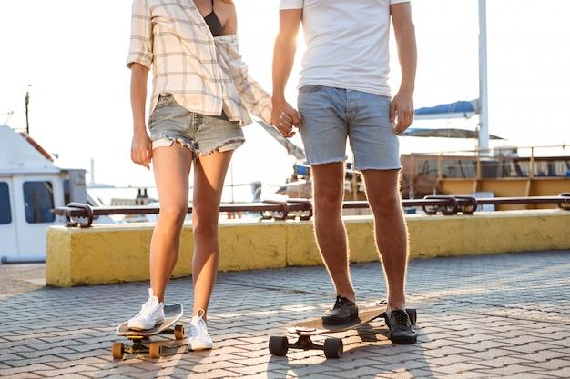 Молодая красивая пара прогулки на берегу моря, скейтбординг. закройте ноги.