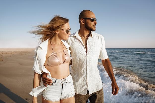Young beautiful couple walking on beach near sea at sunset