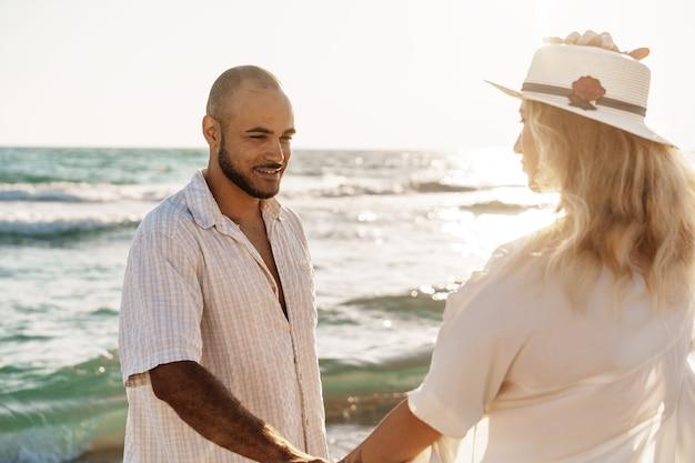日没時に海の近くのビーチを歩く若い美しいカップル