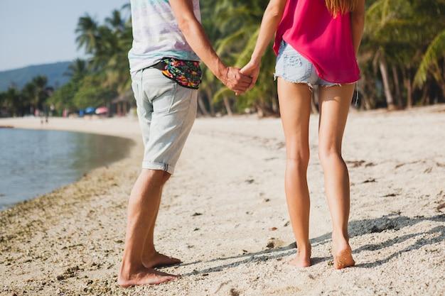 Молодая красивая пара гуляет на тропическом пляже, таиланд, держась за руки, вид со спины, хипстерский наряд, повседневный стиль, медовая луна, отпуск, лето, романтическое настроение, ноги крупным планом, детали