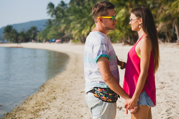 熱帯のビーチ、タイを歩く、抱き締める、笑う、サングラス、楽しむ、流行に敏感な服装、カジュアルなスタイル、新婚旅行、休暇、夏、日当たりの良い、ロマンチックな気分の若い美しいカップル