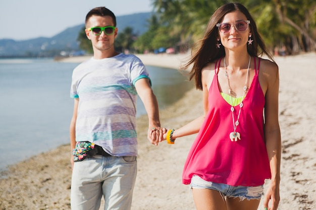 Young beautiful couple walking on tropical beach in thailand, holding hands, smiling, happy, having fun, sunglasses, hipster outfit, casual style, honey moon, vacation, summertime, sunny