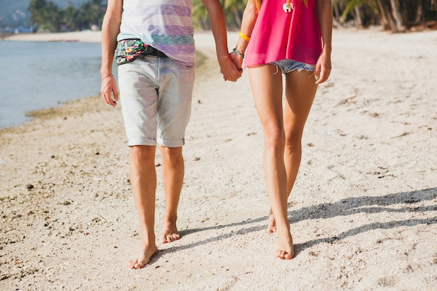 Young beautiful couple walking on tropical beach, thailand, holding hands, view from back, hipster outfit, casual style, honey moon, vacation, summertime, romantic mood, legs close-up, details