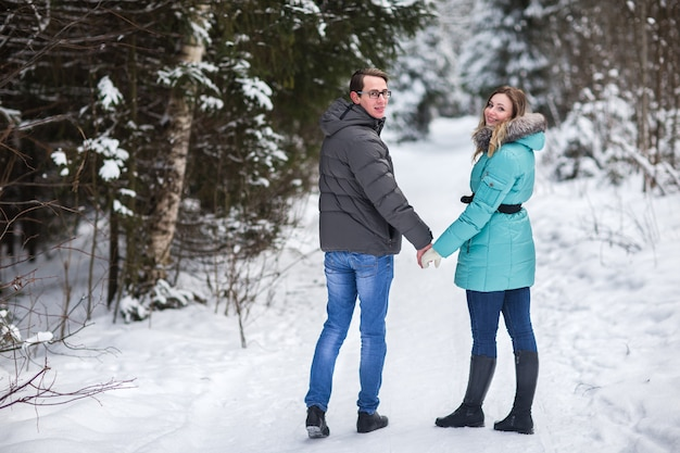 Young beautiful couple walking in winter forest