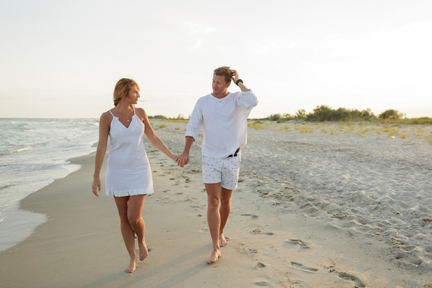 若い美しいカップルは、日没時に海岸沿いを歩きます。