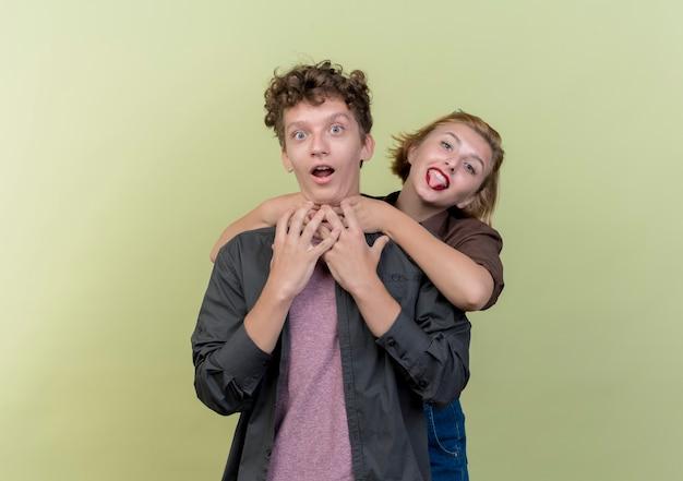 Giovane bella coppia che indossa abiti casual ragazzo e ragazza felice in amore ragazza che abbraccia il suo ragazzo divertendosi insieme sopra la parete chiara