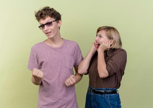 Giovane bella coppia che indossa abiti casual ragazza frustrata guardando il suo ragazzo felice in piedi sopra la parete leggera