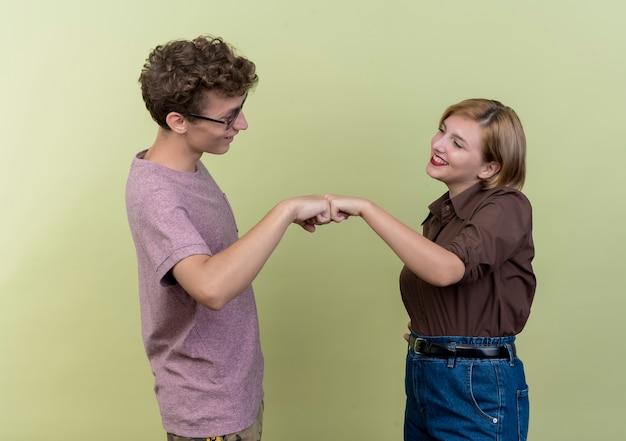 Giovani belle coppie che indossano abiti casual sulla parete chiara
