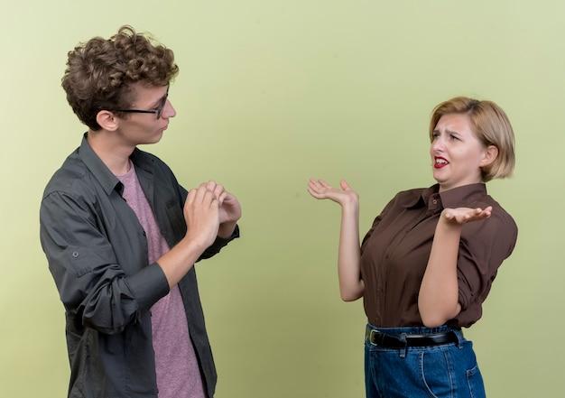 Giovani belle coppie che indossano abiti casual guardando a vicenda litigando in piedi sopra la parete chiara