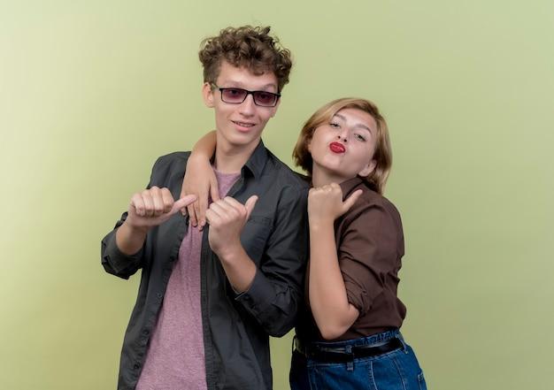 Молодая красивая пара в повседневной одежде, весело улыбаясь, показывает палец вверх, стоя над светлой стеной