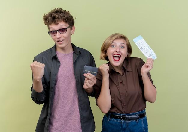 행복하고 흥분된 떨림 주먹 빛 벽 위에 서 credint 카드와 항공 티켓을 들고 캐주얼 옷 남자와 여자를 입고 젊은 아름 다운 부부