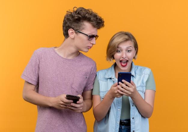 오렌지 벽 위에 서있는 그녀의 여자 친구의 핸드폰 엿보기 캐주얼 옷 남자를 입고 젊은 아름 다운 부부