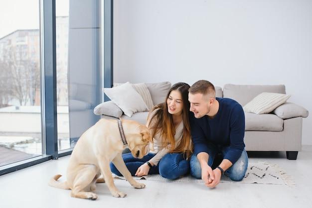 新しい家の床に座っている犬と若い美しいカップル