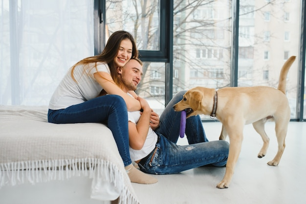 새 집에서 바닥에 앉아 강아지와 함께 젊은 아름 다운 부부