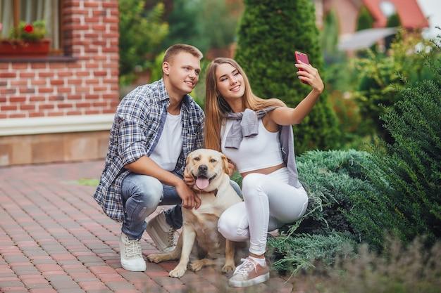 Молодая красивая пара с собакой, делающей селфи