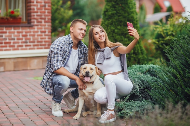 Young beautiful couple with dog taking a selfie