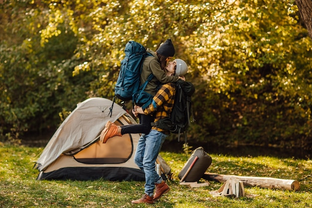 Young beautiful couple with hiking backpack kissing in the forest near tent