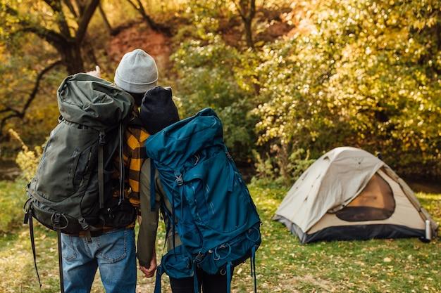 Молодая красивая пара с походными рюкзаками возвращается из похода
