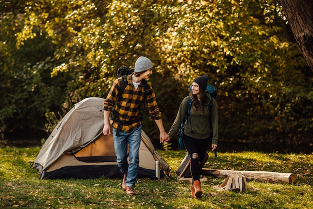 Young beautiful couple with hiking backpacks go trekking