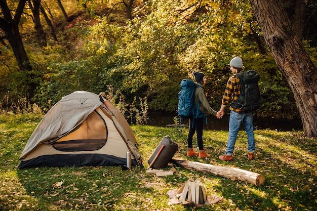La giovane bella coppia con gli zaini da trekking va a fare trekking Foto Gratuite