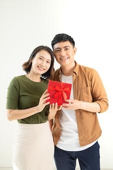 白い壁に隔離されたプレゼントと若い美しいカップル