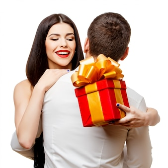 Young beautiful couple with present on white