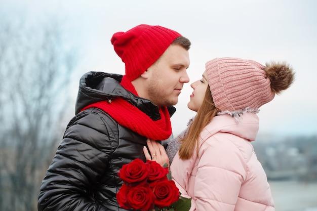屋外で赤いバラと若い美しいカップル