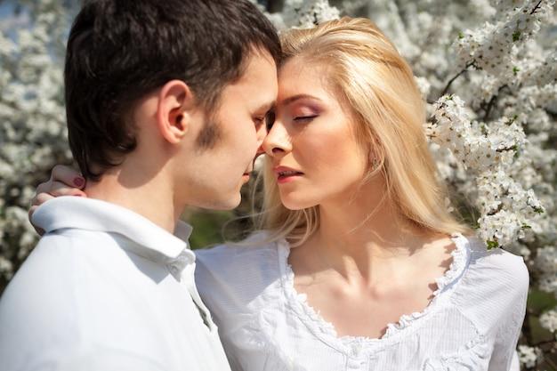 Молодая красивая пара женщина и мужчина целуют друг друга на фоне цветущих веселых деревьев в ясный солнечный день