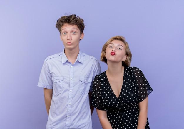 그녀의 남자 친구가 파란색 벽에 서 혼란과 놀란 동안 키스를 불고 젊은 아름 다운 부부 여자 무료 사진