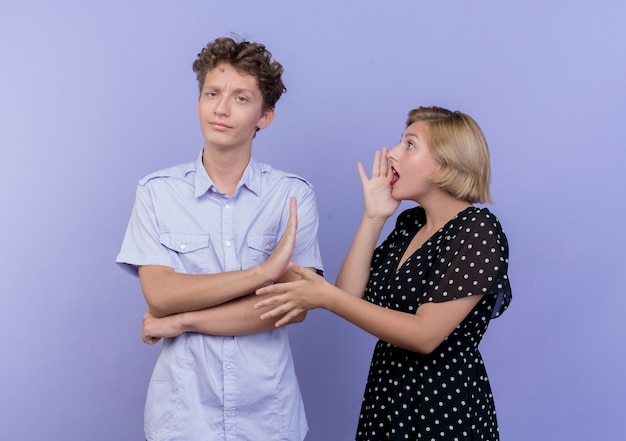 Donna giovane bella coppia che grida sul suo fidanzato mentre mostra il segnale di stop sul blu