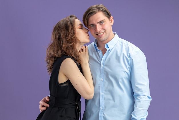 파란색 벽 위에 서있는 발렌타인 데이를 축하하는 그녀의 웃는 남자 친구의 귀에 비밀을 말하고 젊은 아름 다운 부부 여자