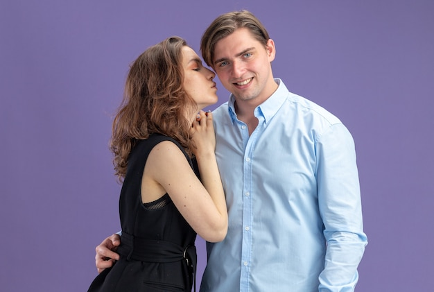 Young beautiful couple woman telling a secret to ear of her smiling boyfriend celebrating valentines day standing over blue wall