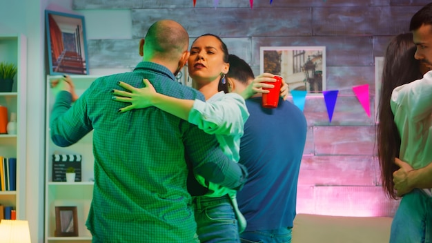 Young beautiful couples dancing on romantic music at the party. neon light.