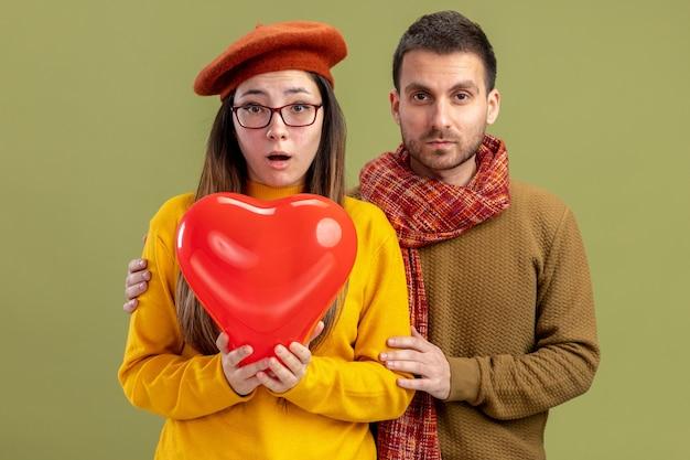 심장 모양의 풍선과 스카프와 남자 베레모에 젊은 아름 다운 couplesurprised 여자 녹색 벽 위에 서있는 축하 발렌타인 데이 놀란