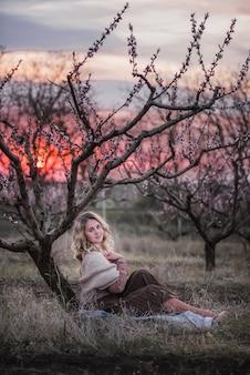 Молодая красивая кудрявая блондинка в коричневой плиссированной юбке, розовой блузке, покрытых плечами вязаным шарфом, сидит в цветущих персиковых садах на закате.