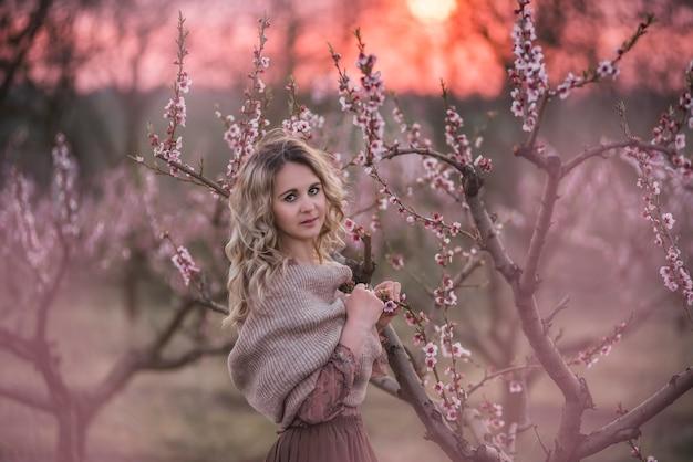 Молодая красивая кудрявая блондинка в коричневой плиссированной юбке, розовая блузка, покрытая плечи вязанным шарфом, стоит в цветущих персиковых садах на закате